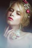 有花的美丽的白肤金发的时尚女孩在脖子和在她的头发,湿裸体构成 秀丽表面 免版税库存照片