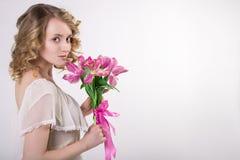 有花的美丽的白肤金发的春天女孩 库存图片