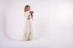 有花的美丽的白肤金发的春天女孩 免版税图库摄影