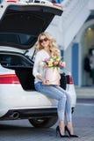 有花的美丽的金发碧眼的女人在礼物盒 免版税库存图片