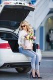 有花的美丽的金发碧眼的女人在礼物盒 库存图片