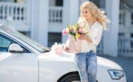 有花的美丽的金发碧眼的女人在礼物盒 免版税图库摄影