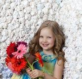有花的美丽的长发女孩在颜色 免版税库存图片