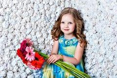 有花的美丽的长发女孩在颜色 免版税库存照片