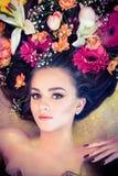 有花的肉欲的妇女在她的在金黄背景的头发 库存图片