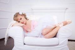 有花的芭蕾舞女演员在她的说谎在一把白色椅子的头发 免版税库存照片