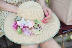 有花的草帽在女孩的手上 免版税库存照片