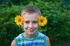 有花的逗人喜爱的男孩在获得的耳朵乐趣 库存照片