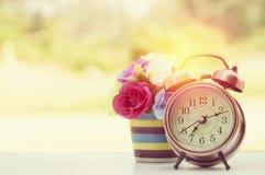 有花的闹钟在木头 库存图片