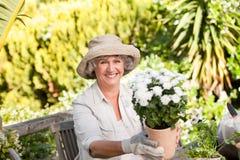 有花的高级妇女在她的庭院里 免版税库存照片