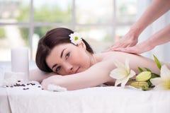 有花的轻松的妇女在温泉中心享用 免版税库存照片