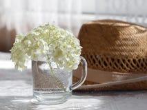 有花的玻璃杯子在柳条帽子背景 免版税库存照片
