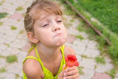 有花的滑稽的女孩在她的手上拉扯了面孔在乞求 免版税库存图片
