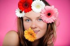 有花的年轻美丽的女孩在她的嘴和她的头发 与明亮的颜色的演播室画象 秀丽和青年概念 库存照片