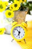 有花的黄色闹钟 免版税图库摄影