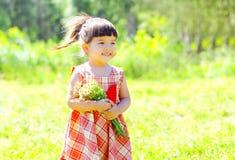 有花的画象愉快的微笑的小女孩孩子在夏天 免版税库存照片