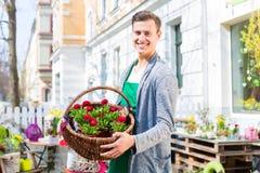 有花篮子的卖花人在商店卖 免版税库存照片