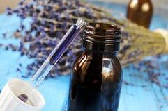 有花精华和淡紫色的吸管瓶开花 免版税库存图片