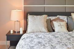 有花纹花样枕头和装饰台灯的豪华卧室 免版税库存图片