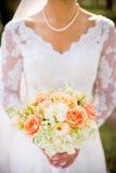 有花美丽的橙色,桃红色和白色婚礼花束的传统新娘  库存照片