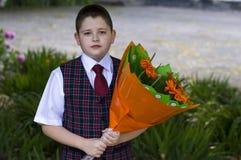 有花美丽的花束的可爱的学校学生, 9月1日的一个主题 免版税库存照片