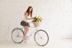 有花自行车和篮子的可爱的女孩  库存图片