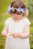 有花花圈的小孩女孩在春黄菊猜测 库存图片