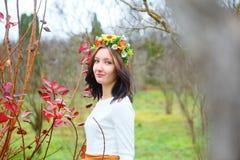 有花花圈的深色的女孩在秋天公园 免版税库存图片