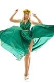 有花花圈的美丽的女孩在一件绿色礼服的 免版税库存图片