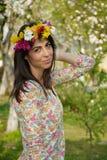 有花花圈的美丽的深色的妇女在春天庭院 免版税图库摄影