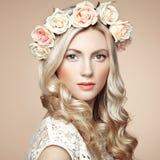 有花花圈的美丽的白肤金发的妇女在她的头 免版税库存照片