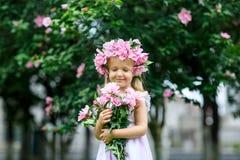 有花花圈的逗人喜爱的微笑的女孩在公园 户外可爱的小孩子画象  ?? r 免版税库存图片