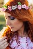 有花花圈的年轻红发妇女在日落光芒的  库存图片