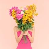 有花花束的女孩在她的手上 库存照片