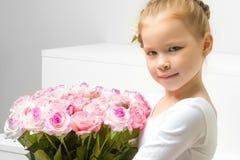 有花花束的小女孩坐一个白色楼梯 库存照片
