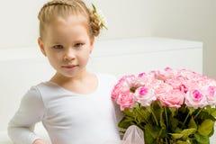 有花花束的小女孩坐一个白色楼梯 免版税图库摄影