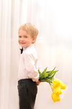 有花花束的小白肤金发的男孩  免版税库存图片