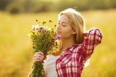 有花花束的愉快的美丽的女孩  免版税库存照片