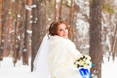 有花花束的新娘在冬天森林里 免版税库存照片