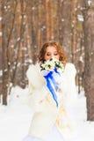 有花花束的新娘在冬天森林里 库存图片