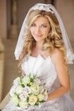 有花花束的,婚姻的m美丽的微笑的新娘妇女 免版税库存图片
