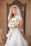 有花花束的,婚姻的m美丽的微笑的新娘妇女 免版税库存照片