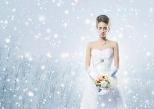有花花束的年轻和美丽的新娘在雪 免版税库存照片