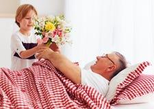 有花花束的年轻孙子在医院病房里来拜访他病的祖父 免版税库存照片