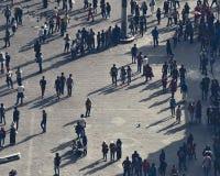 有花费他们的业余时间的每日人生的人人群的城市广场,互相互动 库存照片