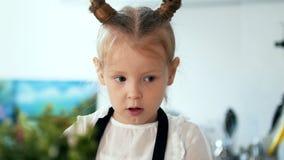 有花费时间的母亲的白肤金发的小女孩在烹调早餐期间在厨房里 影视素材