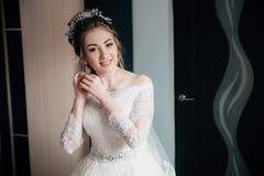 有花边的白色礼服和面纱的新娘去仪式 投入在耳环和微笑的女孩的画象 库存图片