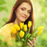有花郁金香花束的美丽的妇女  免版税库存图片