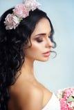 有花饰的美丽的女孩在她的在蓝色背景的头发 一名美丽的妇女的画象婚礼礼服的 免版税库存图片