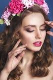 有花饰的美丽的女孩在她的在蓝色背景的头发 花妇女花圈 秀丽表面 时尚phot 库存照片